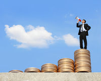 I want be rich. Happy business man using megaphone shouting on money stairs with blue sky background, asian stock photography