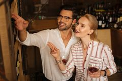 Joyful young woman choosing wine with a sommelier. I want the best. Joyful young women smiling while choosing wine together with a sommelier royalty free stock photography