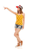I Want This. Confident smiling young woman in yellow dotted shirt, jeans shorts, red sun visor and brown sneakers standing, pointing and looking away. Full Stock Image