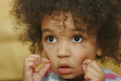 I Want Dimples Please. A beautiful young mixed race girl making dimples in her cheeks stock images