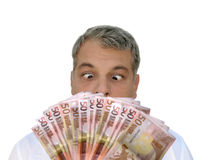 I want that money!!. A man looking with greed at a pile of money Stock Photography