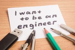 I want to be an engineer inscription in English. Bee lie the tools necessary for this profession Stock Photo