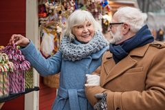 Cheerful old couple buying sweets on street stock images