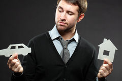 I want to buy a car. Serious young businessman thinking to buy a car instead of house stock photo