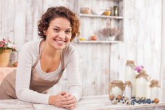 I want to cook something interesting and tasty. Beautiful young woman is standing in the kitchen and leaning on the tables. She is looking at camera and smiling Stock Image