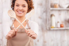 I want to cook something new and tasty. Cheerful young woman is cooking in the kitchen. She is holding two wood spoons and crossing them for fun. The lady is royalty free stock image