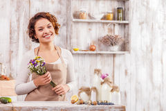 I want to cook something sweet and tasty. Cheerful young woman is cooking in the kitchen. She is sitting at table near healthy products and holding flowers. The Stock Images
