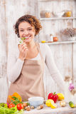 I want to cook something very tasty. Attractive young woman is cooking in the kitchen. She is standing and smiling. The lady is eating parsley with pleasure Royalty Free Stock Photo