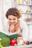 I want to cook something very tasty. Cheerful young woman is reading a recipe from the book in the kitchen. She is standing near a table with a lot of healthy royalty free stock photo