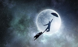 I want to fly away. Mixed media. Silhouette of men flying on umbrella against full moon background. Mixed media Stock Photo