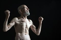 I was strong. Old strong man on black background stock photography