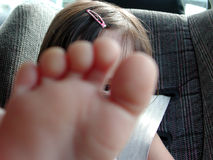 I am watching you. A little girl watching at you between her toes, focus on her eye Stock Photo