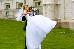 I will carry you in my arms. Laughing the newlyweds on the green grass - the groom lifts the bride in his arms Royalty Free Stock Image