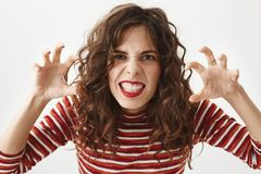 I will eat you. Close-up shot of childish woman bending towards camera with grimace and holding hands as if it is claws. And she want to catch someone, trying Royalty Free Stock Image