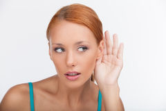 I will keep your secret. Beautiful young woman listening to the Royalty Free Stock Photos