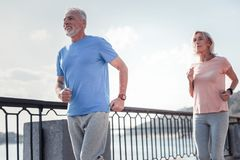 Pleasant handsome man smiling and running. I will lead. Pleasant handsome senior men having morning exercises on the quay smiling and running with a woman Royalty Free Stock Photo