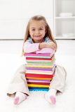 I will learn all this wisdom. Little girl with lots of colorful books Stock Photography