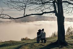 I will never let you go!. Rear view of young couple enjoying perfect view of mountain range while sitting on the bench Royalty Free Stock Photography