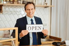 Confident reliable man looking straight and demonstrating the plate. I will not let down. Confident reliable pleasant man standing in his own shop looking Royalty Free Stock Photography