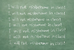 I will not misbehave in class!. Large XXL image of an old chalkboard with the sentence I will not misbehave in class written over and over again Royalty Free Stock Photos