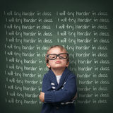 I will try harder in class. Naughty schoolboy with lines written on a blackboard reading I will try harder in class. Detention and school discipline / punishment royalty free stock photo