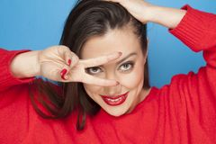 I win. Beautiful woman in red blouse making victory gesture on a blue background Royalty Free Stock Photography