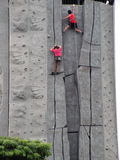 I win - Rock climbing. Taken at a rock climbing wall, one raced to the top and the other can only cling on in despair Stock Images