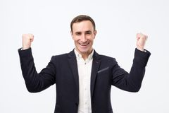 Pleased and happy young italian man is smiling broadly and showing victory sign with both hands. stock photography