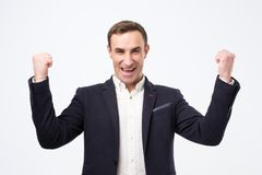 Pleased and happy young italian man is smiling broadly and showi stock image