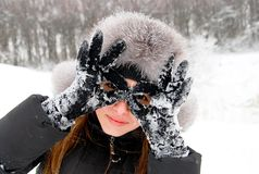I am a winter Batman!. Beautiful girl in winter clothing holds her hands like sunglasses Royalty Free Stock Photography