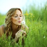 I wish. Young woman makes a wish blowing on dandelion royalty free stock photos