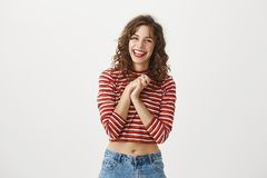 I wish my boyfriend would be like you. Portrait of attractive young female student in stylish outfit, laughing and. Holding clasped hands on chest as if being Royalty Free Stock Photo