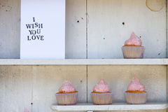 I wish you love. White vintage shelf with i wish you love card and strawberry cream cupcake royalty free stock photo
