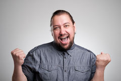 I won Happy young man gesturing and smiling while standing against gray background Royalty Free Stock Photo
