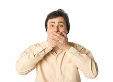 I won't tell you. Man covering his mouth with hands, white background Stock Photos