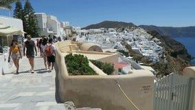 Ia, Santorini/GRECIA 15 maggio 2017: Paesaggio urbano di Ia, città all'isola Grecia di Santorini La gente che cammina lungo la pa stock footage