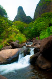 Iao Needle Stream Maui Hawaii. Vibrant stream with Iao Needle in background. People are seen walking across the bridge royalty free stock photography