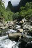 Iao Stream And Needle. Iao Stream with visitors standing on a bridge in the distance.  Further beyond is the Iao Needle.  Located in the Iao Valley on the island Stock Images