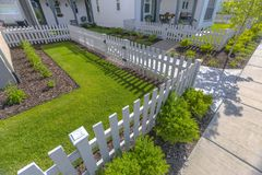 Iarda anteriore con i prati inglesi ed arbusti con il recinto bianco Immagini Stock Libere da Diritti