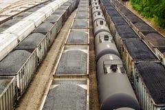 Iarda della ferrovia con i vagonetti della tramoggia per il carbone e del carro armato Immagini Stock Libere da Diritti