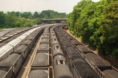 Iarda della ferrovia con i vagonetti della tramoggia per il carbone e del carro armato Immagini Stock