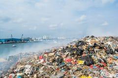Iarda di ciarpame vicino alla vista del porto in pieno di fumo, della lettiera, delle bottiglie di plastica, dei rifiuti e dei ri Immagine Stock