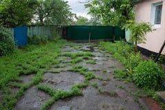Iarda rurale dopo la pioggia invasa con erba fotografia stock