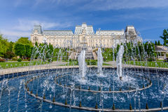 IASI, ROMANIA - 23 MAY 2015: Iasi Cultural Palace being restaurated with a beautiful green park on a sunny spring day with dramati. C sky on background Royalty Free Stock Photo