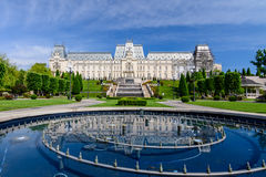 IASI, ROMANIA - 23 MAY 2015: Iasi Cultural Palace being restaurated with a beautiful green park on a sunny spring day with dramati. C sky on background Royalty Free Stock Images