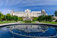 IASI, RUMÄNIEN - 23. MAI 2015: Kultureller Palast Iasi, der mit einem schönen grünen Park an einem sonnigen Frühlingstag mit dram Lizenzfreie Stockbilder