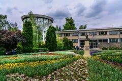 IASI, RUMANIA - 28 DE JUNIO DE 2015: Flores decorativas hermosas delante de la entrada principal del jardín botánico Imagen de archivo libre de regalías