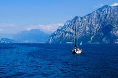 Iate branco em um lago azul da montanha em Malcesine, Itália fotografia de stock royalty free