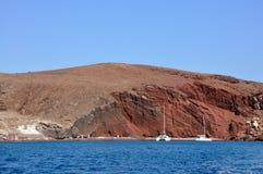 Iate brancos e a praia vermelha famosa na ilha de Santorini, Grécia Fotografia de Stock Royalty Free