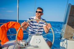 Iate da navigação do homem novo Fotos de Stock Royalty Free